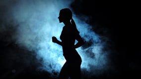 Funzionamento di signora su un riflettore fumoso su fondo nero Siluetta Movimento lento