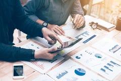 Funzionamento e collega della persona di due imprenditori che analizzano i dati per fotografia stock