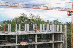 Funzionamento e gru del gruppo del lavoratore della costruzione sull'alloggio della costruzione del terreno alto nel posto di lav Immagini Stock Libere da Diritti