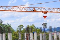 Funzionamento e gru del gruppo del lavoratore della costruzione sull'alloggio della costruzione del terreno alto nel posto di lav Fotografia Stock