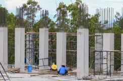Funzionamento e gru del gruppo del lavoratore della costruzione sull'alloggio della costruzione del terreno alto nel posto di lav Immagine Stock