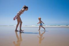 Funzionamento felice del bambino alla spiaggia ed alla madre Fotografie Stock Libere da Diritti