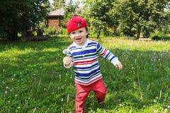 Funzionamento felice del bambino con il blowball Fotografia Stock