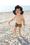 Funzionamento felice del bambino lungo la spiaggia dei ciottoli Fotografie Stock Libere da Diritti