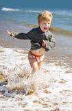 Funzionamento felice del bambino sulla spiaggia del mare Immagini Stock Libere da Diritti