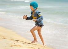 Funzionamento felice del bambino sulla spiaggia del mare Fotografie Stock