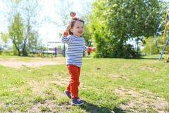 Funzionamento felice del piccolo bambino con il lecca lecca di estate Immagini Stock Libere da Diritti