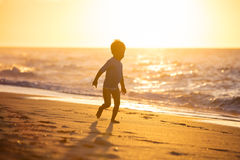 Funzionamento felice del ragazzino sulla spiaggia Immagini Stock