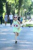 Funzionamento felice della bambina nel parco della città Emitions puerili positivi fotografia stock