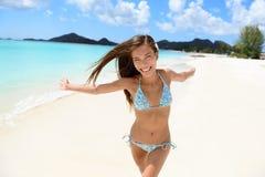 Funzionamento felice della donna del bikini della spiaggia con l'aspirazione fotografia stock libera da diritti