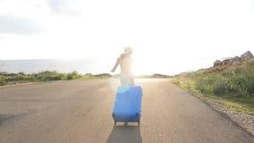 Funzionamento felice della donna del viaggiatore con la valigia