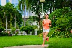Funzionamento felice della donna di forma fisica al parco della città fotografie stock libere da diritti