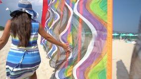Funzionamento felice della donna sulla spiaggia e giocare con gli aquiloni del vento archivi video