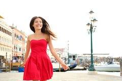 Funzionamento felice della donna in vestito da estate, Venezia, Italia Immagine Stock