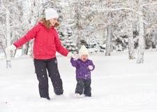 Funzionamento felice della figlia della madre e della neonata della famiglia, passeggiata e giocare nella neve di inverno Fotografia Stock