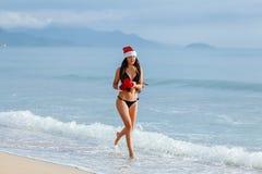 Funzionamento felice della ragazza con il regalo di chrismas sulla spiaggia Immagine Stock Libera da Diritti