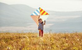 Funzionamento felice della ragazza del bambino con l'aquilone al tramonto all'aperto immagine stock