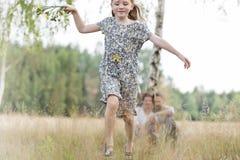 Funzionamento felice della ragazza mentre genitori che si siedono sul campo fotografia stock libera da diritti