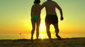 Funzionamento felice delle coppie lungo la spiaggia che si tiene per mano su un fondo di tramonto al rallentatore Siluette di una stock footage