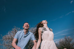 Funzionamento felice delle coppie nel giardino della fioritura che tiene congiuntamente Fotografia Stock