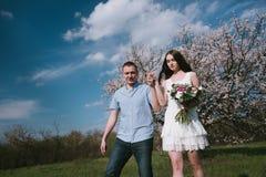 Funzionamento felice delle coppie nel giardino della fioritura che tiene congiuntamente Fotografie Stock Libere da Diritti