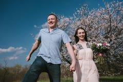 Funzionamento felice delle coppie nel giardino della fioritura che tiene congiuntamente Fotografia Stock Libera da Diritti