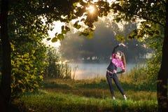 Funzionamento femminile del corridore in natura durante l'alba Fotografie Stock