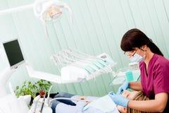 Funzionamento femminile del dentista Fotografia Stock