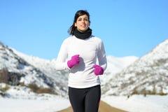 Funzionamento femminile dell'atleta della neve di inverno Fotografie Stock