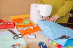 Funzionamento femminile dello stilista Lavoro del sarto da donna sulla macchina per cucire Sarto che fa un indumento in posto di  immagini stock libere da diritti