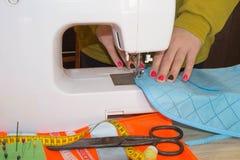 Funzionamento femminile dello stilista Lavoro del sarto da donna sulla macchina per cucire Sarto che fa un indumento in posto di  fotografia stock
