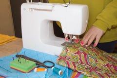 Funzionamento femminile dello stilista Lavoro del sarto da donna sulla macchina per cucire Sarto che fa un indumento in posto di  immagine stock