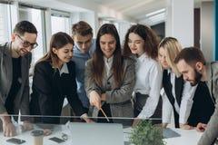 Funzionamento insieme Gruppo di giovani moderni nell'abbigliamento casual astuto che discutono affare e che sorridono nell'uffici immagini stock