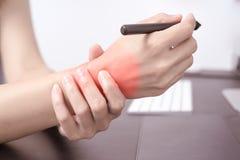Funzionamento lungo del topo della penna di uso di dolore del braccio del polso della donna sanità di sindrome dell'ufficio e con Fotografia Stock