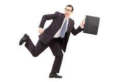 Funzionamento maschio spaventato dell'uomo d'affari a partire da qualcosa Immagini Stock Libere da Diritti