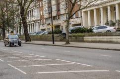 Funzionamento nero tipico del taxi di Londra sulla strada, nei precedenti Fotografia Stock