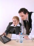 Funzionamento per due persone sul computer portatile all'ufficio Immagine Stock