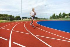 Funzionamento risoluto della donna sulle piste di sport immagine stock