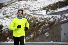 Funzionamento sano dell'uomo di sport sulla strada alle montagne della neve nell'allenamento duro del corridore della traccia nel Immagini Stock Libere da Diritti
