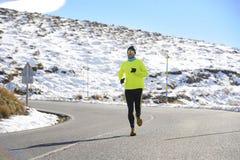 Funzionamento sano dell'uomo di sport sulla strada alle montagne della neve nell'allenamento duro del corridore della traccia nel Immagine Stock