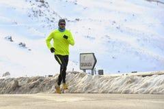 Funzionamento sano dell'uomo di sport sulla strada asfaltata alle montagne della neve nell'allenamento duro del corridore della t Fotografie Stock Libere da Diritti