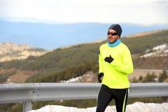 Funzionamento sano dell'uomo di sport sulla strada asfaltata alle montagne della neve nell'allenamento duro del corridore della t Immagini Stock