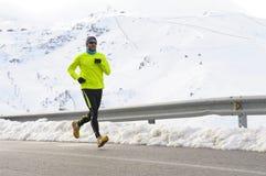 Funzionamento sano dell'uomo di sport sulla strada asfaltata alle montagne della neve nell'allenamento duro del corridore della t Immagini Stock Libere da Diritti