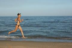 Funzionamento sportivo attivo della donna lungo la spuma dell'oceano dallo stagno di acqua per tenere misura e salute Fondo nero  Immagini Stock Libere da Diritti