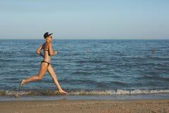 Funzionamento sportivo attivo della donna lungo la spuma dell'oceano dallo stagno di acqua per tenere misura e salute Fondo nero  Immagini Stock