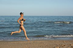 Funzionamento sportivo attivo della donna lungo la spuma dell'oceano dallo stagno di acqua per tenere misura e salute Fondo nero  Fotografie Stock Libere da Diritti