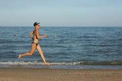 Funzionamento sportivo attivo della donna lungo la spuma dell'oceano dallo stagno di acqua per tenere misura e salute Fondo nero  Fotografia Stock