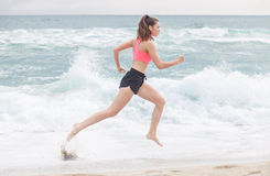 Funzionamento sportivo attraente della donna lungo la spiaggia Fotografia Stock