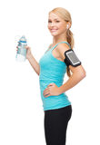 Funzionamento sportivo della donna con lo smartphone e le cuffie Fotografie Stock