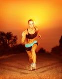 Funzionamento sportivo della donna sul tramonto Immagine Stock